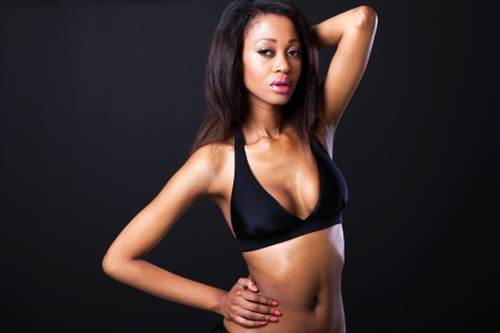 pretty african model in bikini on black background photo