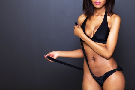 sexy young african american woman untie bikini panties on black background photo