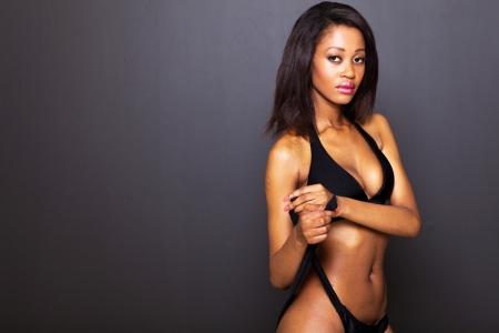 african bikini: sexy young african american woman on black background