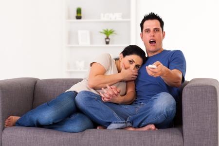 pareja viendo television: joven pareja viendo la película de terror de miedo en casa Foto de archivo