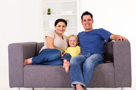 family sofa: young happy family sitting on sofa at home Stock Photo