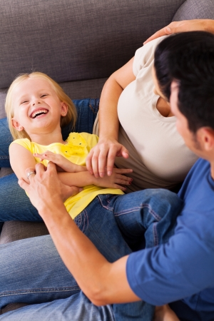 tickling: parents tickling little daughter on sofa Stock Photo