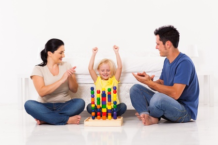 happy little girl playing toys with parents on bedroom floor photo