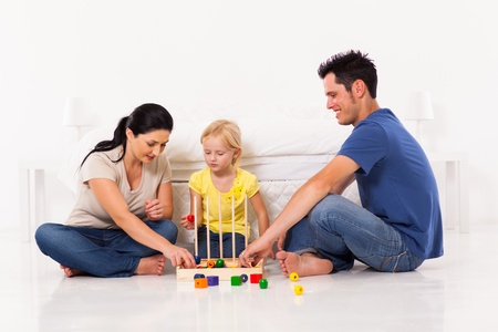 happy family playing toy game with daughter on bedroom floor photo