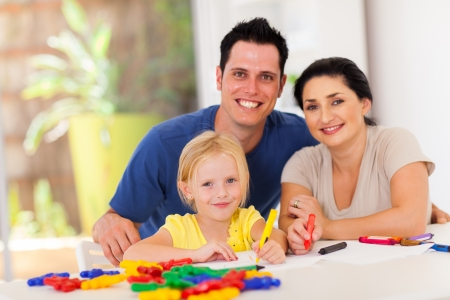 happy parents and little daughter drawing pictures at home photo