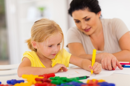 cute little girl drawing with mother at home Stock Photo - 17359274