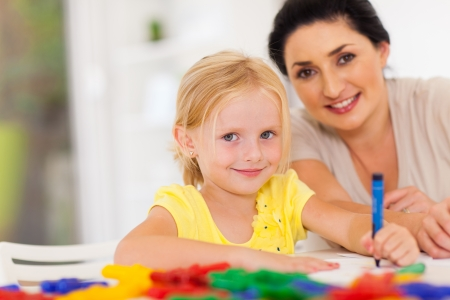 cute little girl drawing with mother at home Stock Photo - 17331674