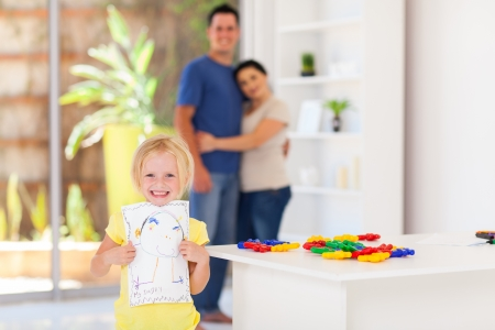 cute little girl showing her drawing in front of parents Stock Photo - 17365204