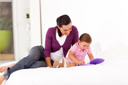 little girl playing toy laptop on bed with mother at home Stock Photo - 17365014