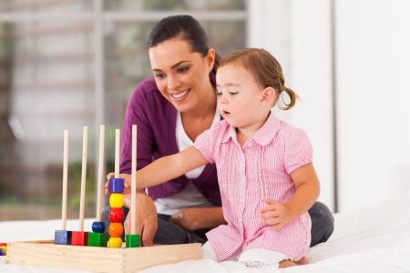 petite fille jouant jouet éducatif avec la mère sur le lit Banque d'images