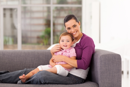 happy mother hugging daughter on sofa Stock Photo - 17364983