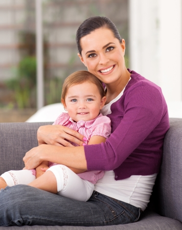 pretty mother hugging cute little daughter on sofa photo