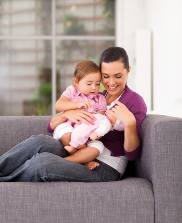modern doll: happy mother playing toy with daughter on sofa at home