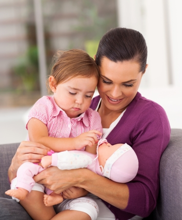 happy mom playing doll with little daughter on sofa Stock Photo - 17365007