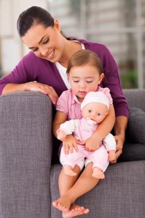 baby doll: cute daughter hugging a doll at home with mother  Stock Photo