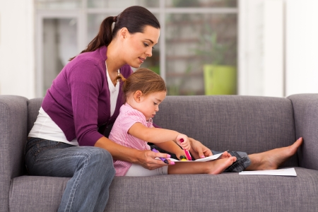 mother teaching daughter drawing on sofa at home photo