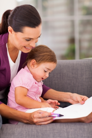 mother teaching little daughter drawing at home photo