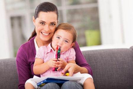 happy mother and little daughter with crayon at home photo