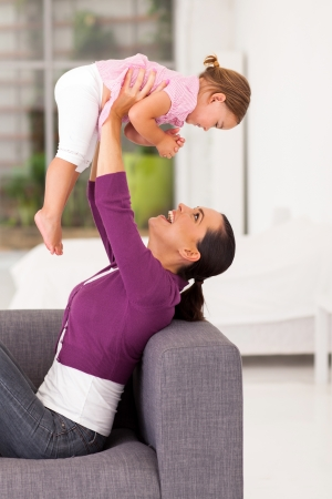 playful mother playing with little daughter at home Stock Photo - 17365185
