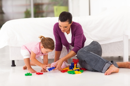 happy mother and daughter playing with toy on bedroom floor Stock Photo - 17331620