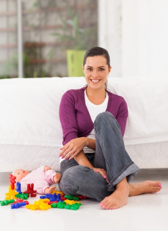 beautiful young mother sitting on bedroom floor Stock Photo - 17331619