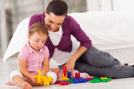 blonde mom: loving mother watching daughter playing with toy