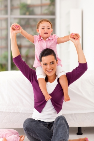 happy little girl sitting on mother's shoulders at home Stock Photo - 17366442