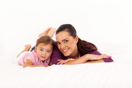 happy mother and baby girl lying on bed photo