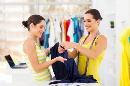 tailors tape: two young female fashion designers choosing fabric Stock Photo
