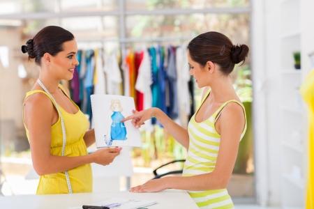working dress: pretty fashion designer showing design to her client
