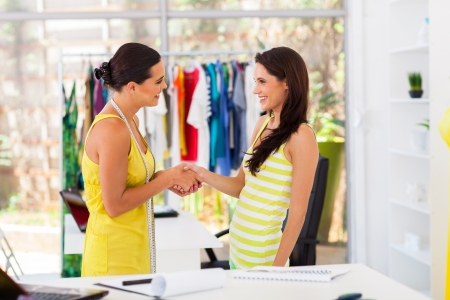handshaking: friendly fashion designer greeting client in studio