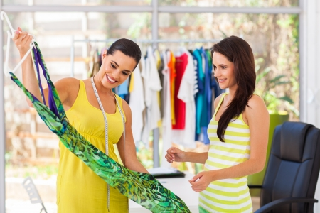 happy fashion designer showing a dress to her customer photo