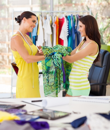 handover: happy dressmaker hand over a dress to her client Stock Photo