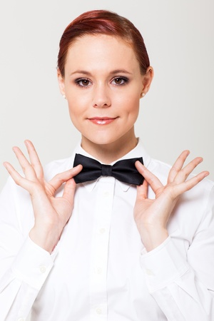 elegant young waitress holding on to bow tie photo