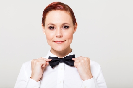 bowtie: beautiful young waitress holding bow tie and smiling Stock Photo