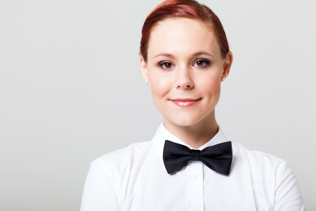 beautiful young waitress with bow tie studio portrait Stock Photo