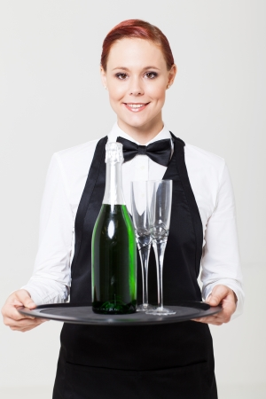 pretty young waitress holding tray with champagne and glass photo