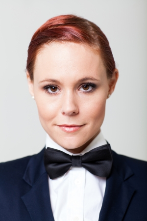 navy blue suit: attractive young woman in suit with bow tie closeup