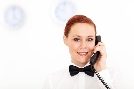 pretty young receptionist working at hotel reception photo