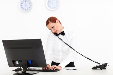 réceptionniste de l'hôtel parlant au téléphone tout en vérifiant sur l'ordinateur Banque d'images