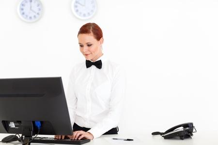 hotel reception: junge Empfangsdame arbeiten an der Hotelrezeption