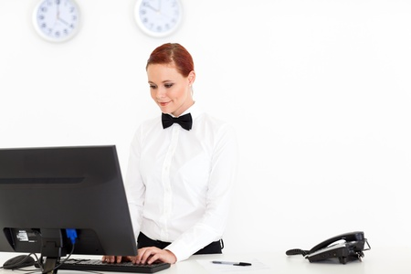 hotel worker: young receptionist working at hotel reception