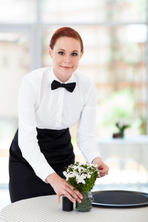 pretty young waitress working in modern restaurant photo