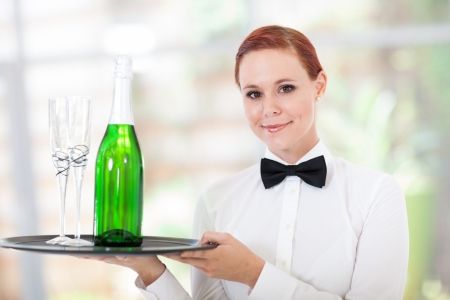pretty young waitress serving champagne in restaurant photo