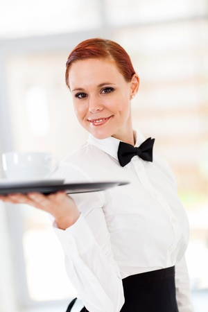 beautiful young waitress serving coffee in restaurant photo