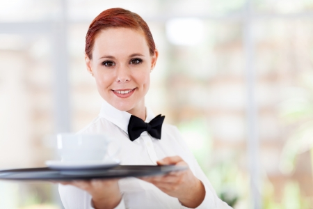 attractive young waitress serving coffee in cafe photo