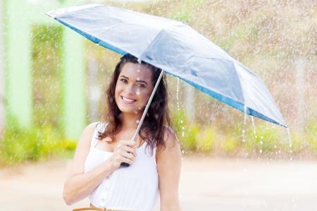 lluvia paraguas: bastante joven en la lluvia con paraguas Foto de archivo
