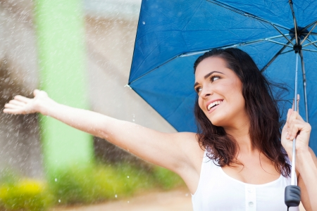 rainy season: attractive young woman having fun in the rain