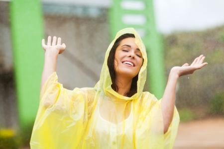 pretty young woman enjoying the rain outdoors photo