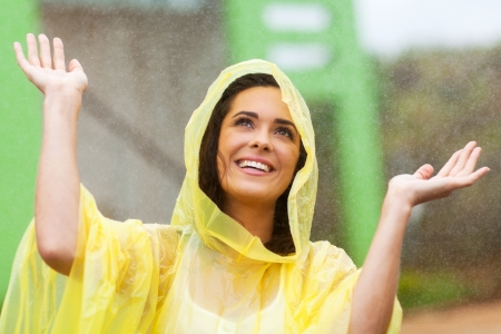 poncho: happy young woman playing in the rain